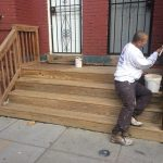 Washington, DC residential wood front porch worker applying stain